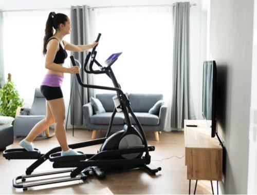 Woman using an elliptical machine at home